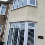 bay windows on front of house with white blinds
