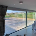 new grey curtains overlooking exterior football pitch in garden